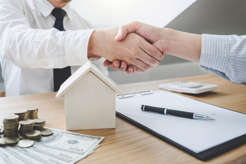 Real estate broker agent and customer shaking hands after signin stock image