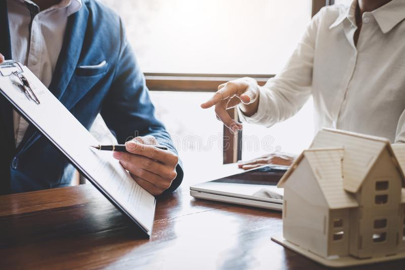 Real estate broker agent presenting and consult to customer to decision making sign insurance form agreement, home model,. Concerning mortgage loan offer for stock image