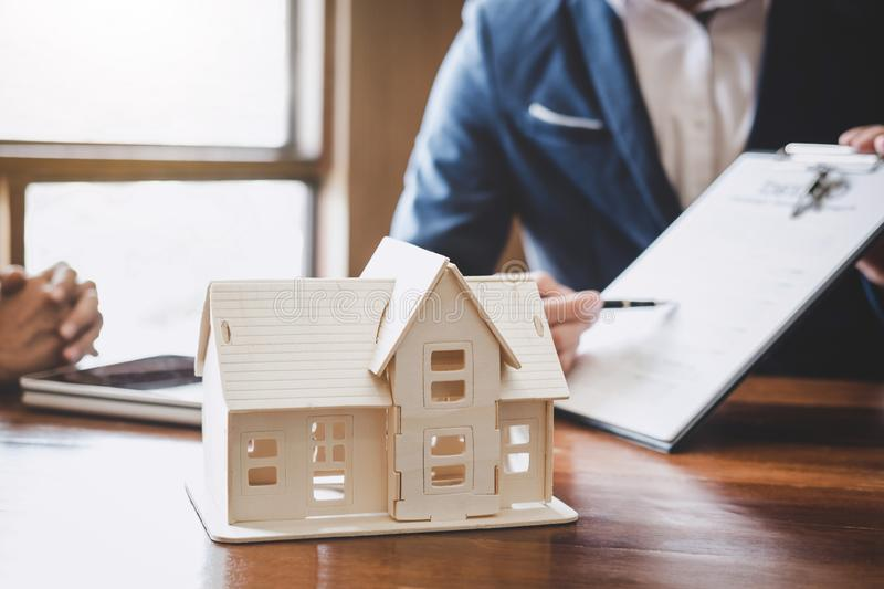 Real estate broker agent presenting and consult to customer to decision making sign insurance form agreement, home model,. Concerning mortgage loan offer for royalty free stock images