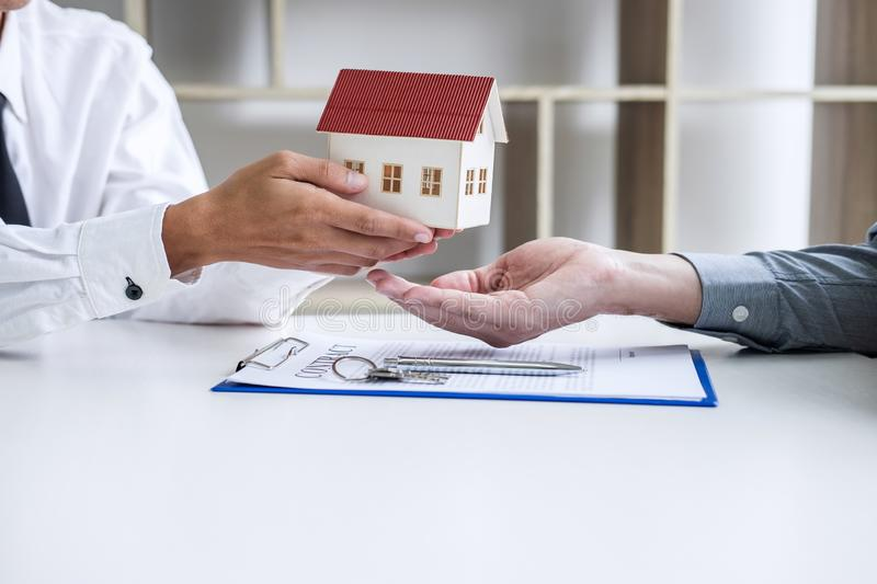 Real estate broker agent presenting and consult to customer to decision making sign insurance form agreement, home model,. Concerning mortgage loan offer for royalty free stock image