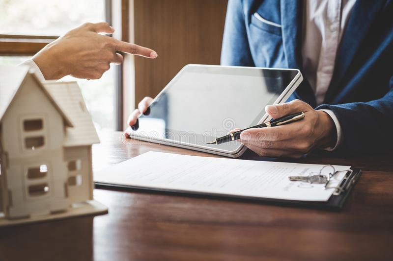 Real estate broker agent presenting and consult to customer to decision making sign insurance form agreement, home model,. Concerning mortgage loan offer for royalty free stock photography