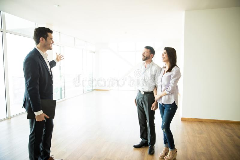 Real Estate Broker Showing Couple A New House. Real estate broker showing mid adult couple a new house stock photography