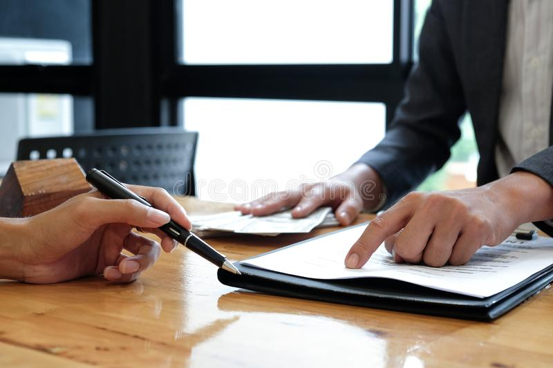 Real estate brokers pointed to signing agreement documents. Real estate brokers pointed to signing agreement documents,Real estate concepts stock image