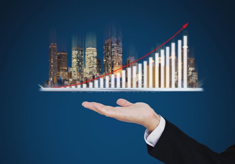 Real estate business investment concept. Businessman hand holding digital tablet with buildings hologram and increasing bar chart stock photos