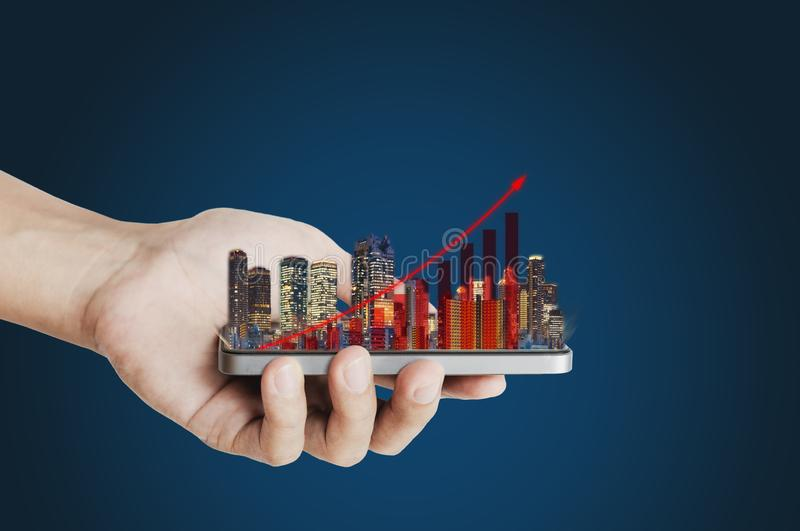 Real estate business investment concept. Hand holding mobile smart phone with buildings hologram and increasing bar chart and grap. Hs stock photos