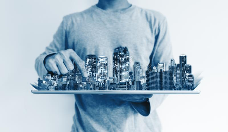 Real estate business and investment, smart building technology. a man using digital tablet with buildings hologram. Real estate business and investment, smart stock image