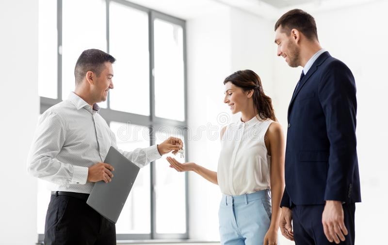 Realtor giving key to customers at new office royalty free stock image