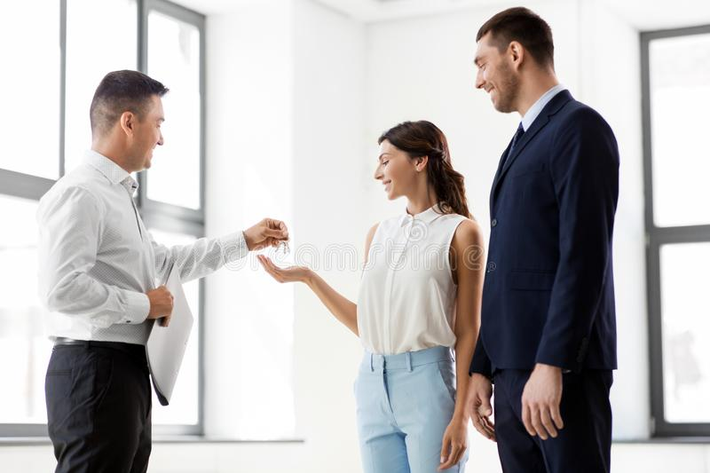 Realtor giving key to customers at new office royalty free stock photos