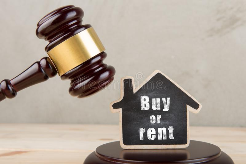 Real estate concept auction gavel and little house with inscription Buy or Rent. Real estate concept -auction gavel and little house with inscription Buy or Rent royalty free stock photography