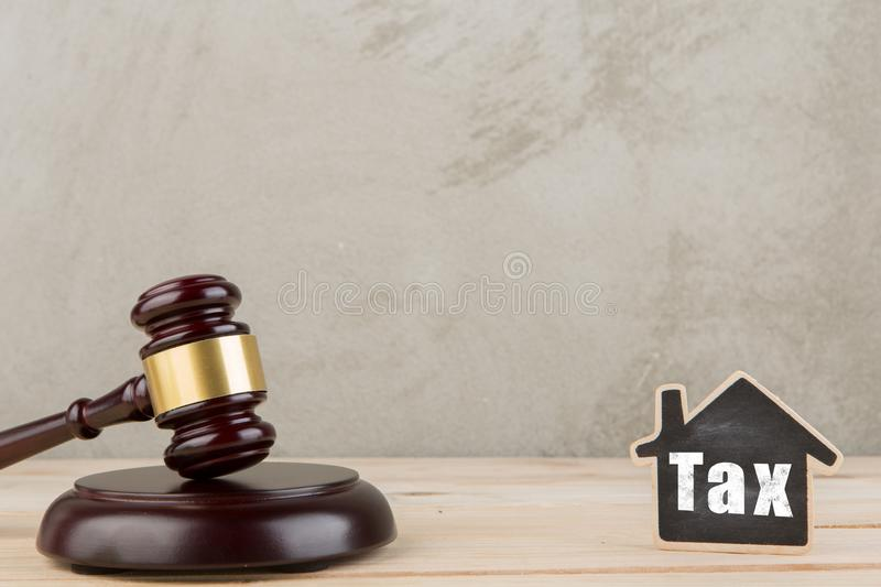 Real estate concept auction gavel and little house with inscription Tax. Real estate concept -auction gavel and little house with inscription Tax, rent, home royalty free stock image