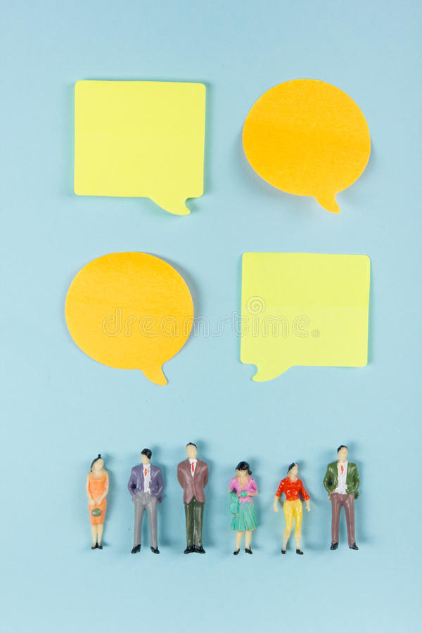 Real Estate concept. Blank speech bubbles and people toy figures Construction, building. Paper model house with key on. Blue background. Top view. Copy space stock image