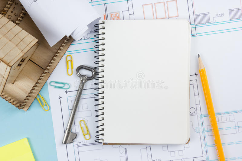 Real estate concept blank white notebook on architectural desk blank white notebook on architectural desk table blueprint background with key malvernweather Choice Image