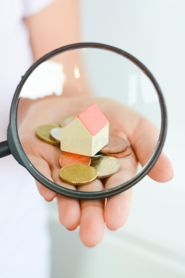 Real estate concept - coins and house architectural model in woman hand under magnifying glass. Real estate concept - coins and house model in woman hand under royalty free stock photo