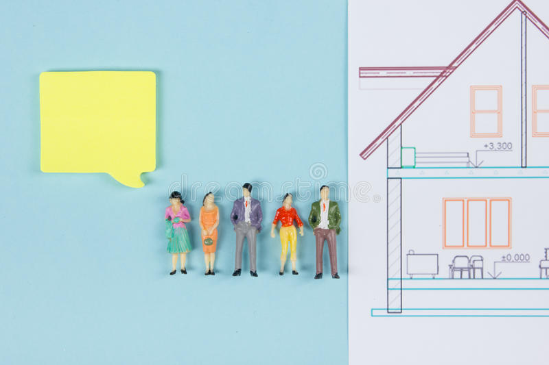 Real Estate concept. Construction building. Blank speech bubbles, people toy figures, paper model house, blueprints with stock photography
