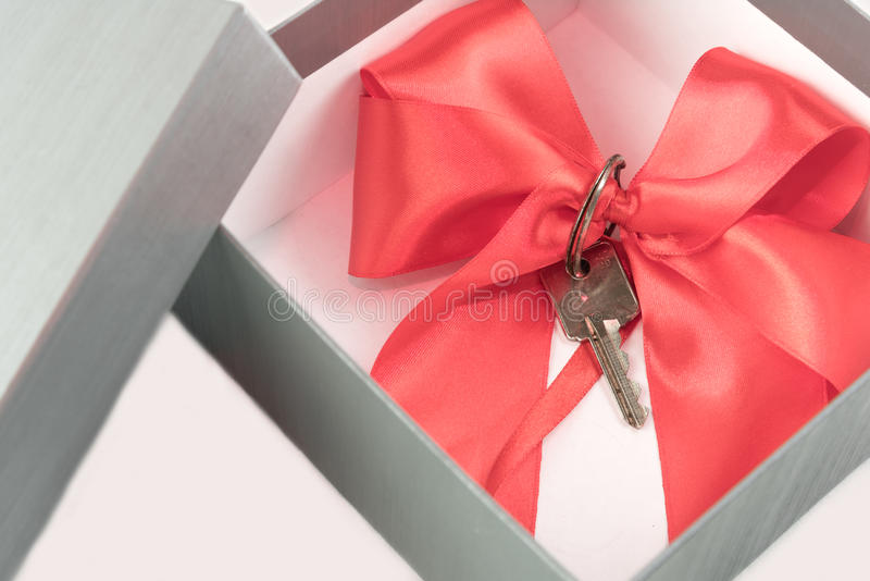 Real estate concept gift in a present box. With a red ribbon royalty free stock photos