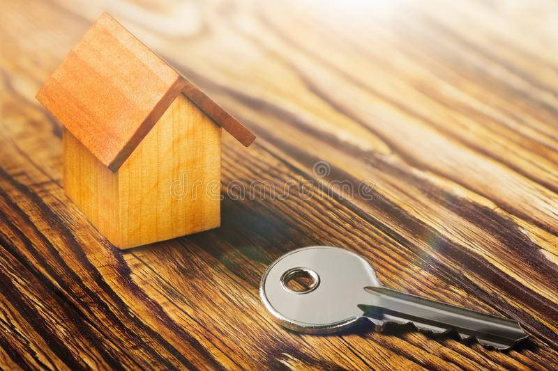 Real estate concept with house and key on wooden background. Idea for real estate concept, personal property a. Real estate concept with small toy wooden house stock image