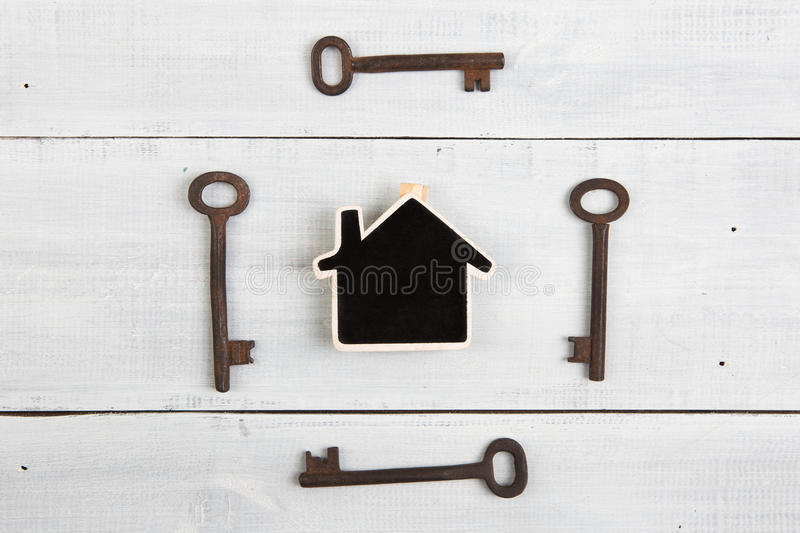 Real estate concept - little house and keys on white wooden desk. Real estate concept - house and keys on white wooden desk royalty free stock image