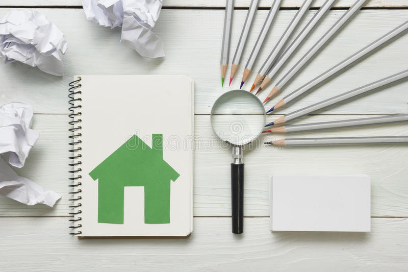 Real estate concept - magnifying glass, pencils and blank business card on wooden table. Copy space for text royalty free stock image