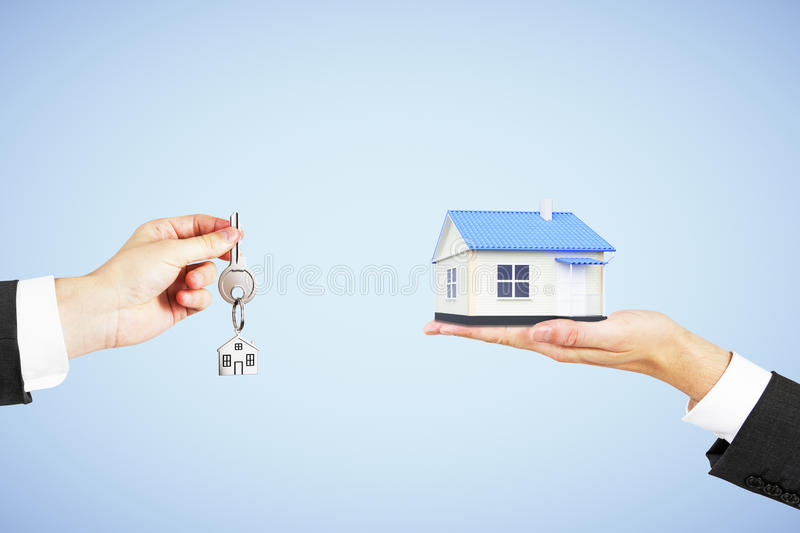 Real estate concept with man hand with key and house in another stock photos