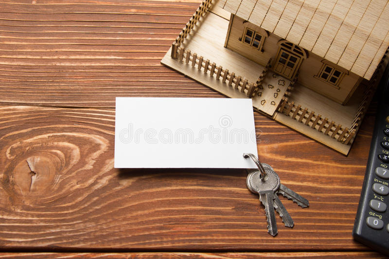 Real Estate Concept. Model house, keys, blank business card and calculator on wooden table. Top view. Model house, keys, blank business card and calculator on stock image