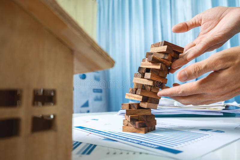 Real estate concept, prevent consultant urgent, wood toy building on business desk table in office. stock photography