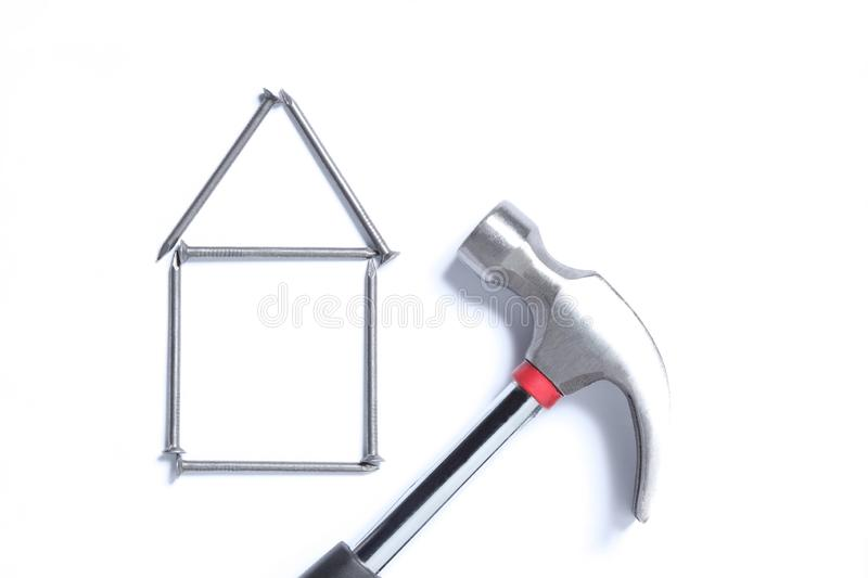 Real estate concept: shape of an house made with nails and an hammer isolated on white background with copy space for your text royalty free stock image
