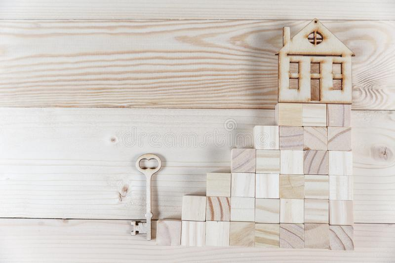 Real estate concept. Small toy wooden house with keys. With copy space stock photos