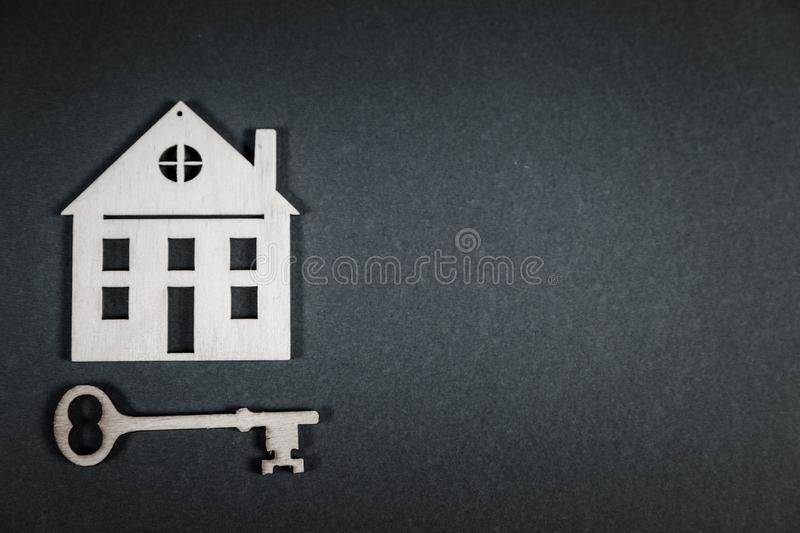 Real estate concept. Small toy wooden house with keys on grey background. With copy space royalty free stock photos