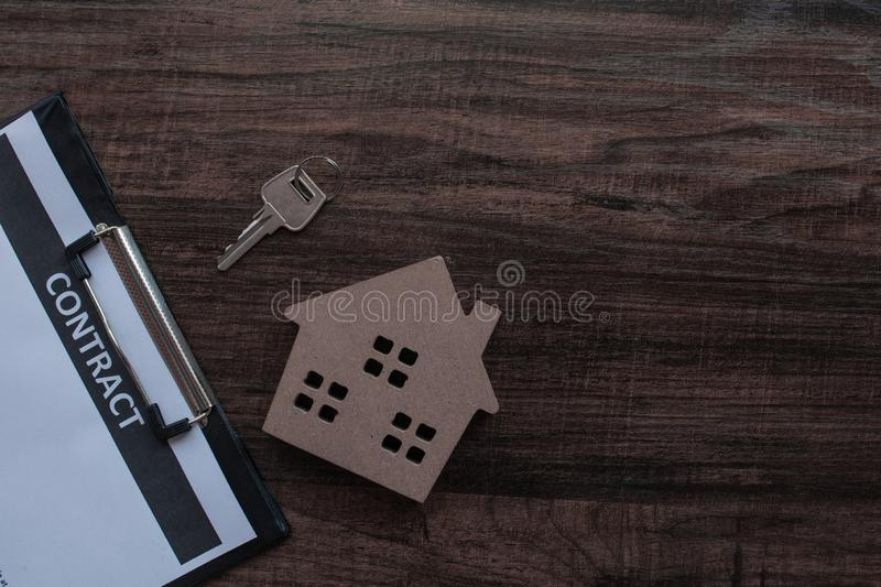 real estate and contract paper with house key on wood table stock image