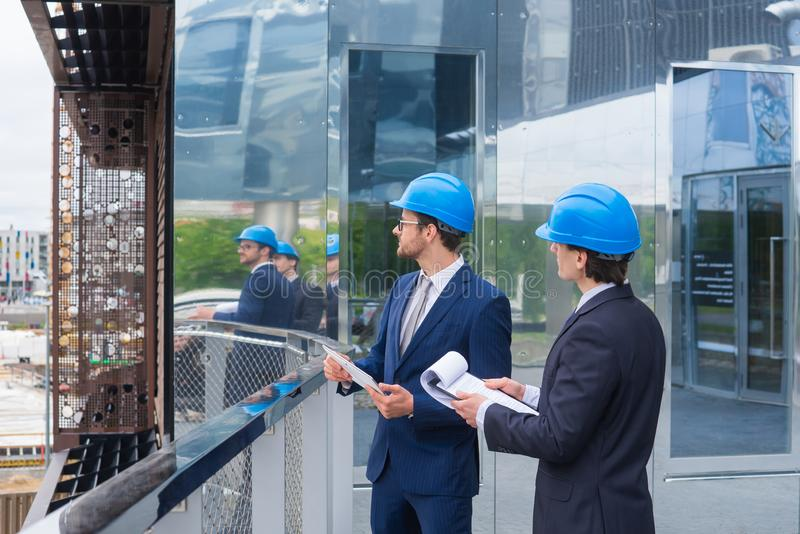 Real estate developers in helmets. New office construction. Confident business men and architect talking in front of royalty free stock images