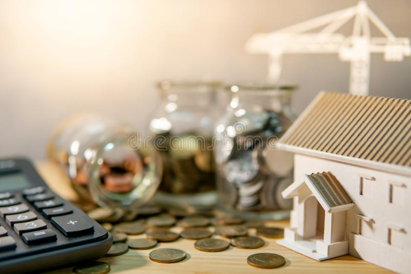 Real estate development or property investment. House and construction crane models, calculator, coins in currency glass jars on the table. Saving money for stock image