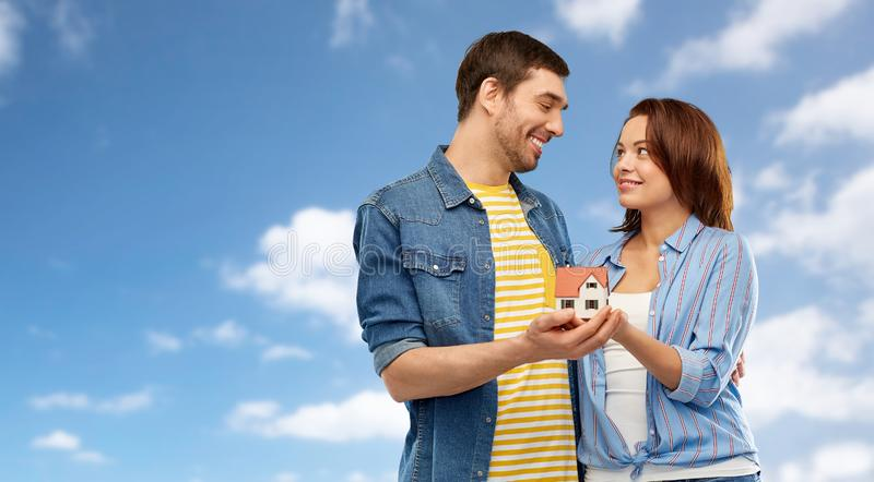 Smiling couple holding house model. Real estate, family and mortgage concept - smiling couple holding house model over blue sky and clouds background stock photography