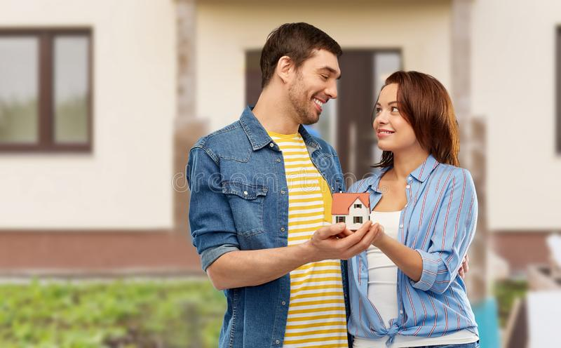 Smiling couple holding house model. Real estate, family and mortgage concept - smiling couple holding house model over home background royalty free stock photos
