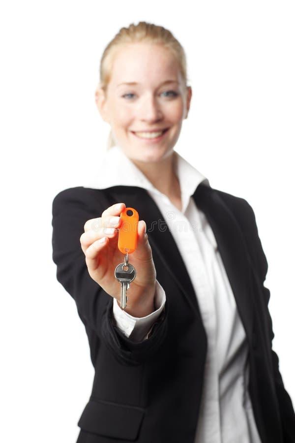 Real Estate-Frau, die einen Schlüssel gibt stockbild