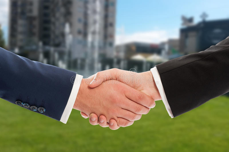 Real estate handshake over building and property for sale background. Real estate handshake over building and green property for sale background stock image