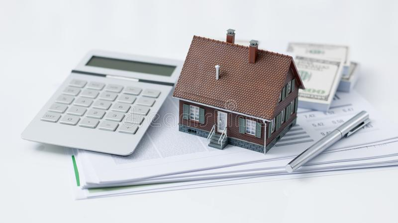 Real estate and home loan. Model house, calculator, cash money and paperwork on a desk: real estate, home loan and investments concept stock photography