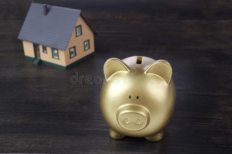 Real estate or home savings - gold piggy bank and house. On wooden background stock photo