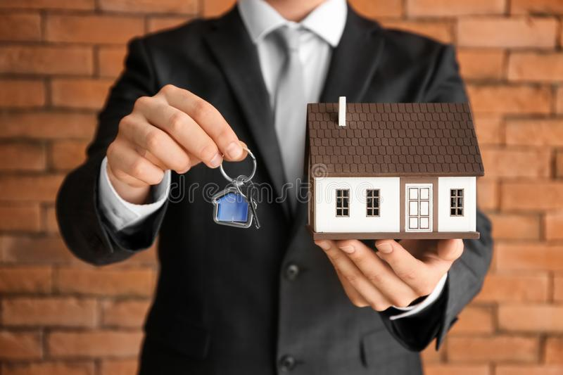 Real estate with house model and key near brick wall, closeup stock photography