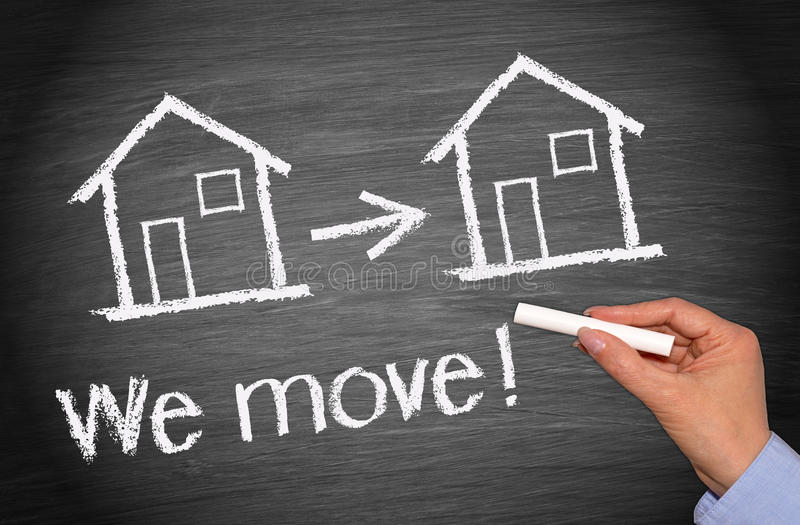 Real estate house move. Hand of woman writing we move with two houses and arrow on blackboard or chalkboard, real estate concept royalty free stock images
