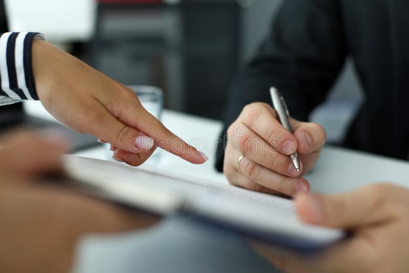Real estate clerk pointing where visitor should sign document. Real estate or insurance clerk pointing finger where visitor should sign document close-up royalty free stock photos