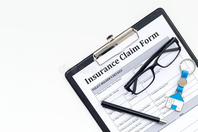 Real estate insurance. Insurance claim form near house keychain on white background top view copy space stock photography
