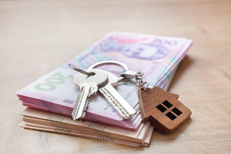 Real estate investing concept. Ukrainian hryvnia, cash or housing. Keys close up. Real estate investing concept. Ukrainian hryvnia, cash or housing. Keys close stock photo