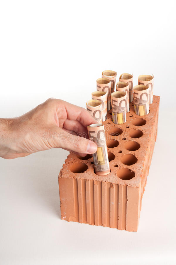 Real estate investment 2 (vertical). A male's hand introducing euro notes into the holes of a perforated brick as if it was a piggy bank or a place to grow notes stock photos