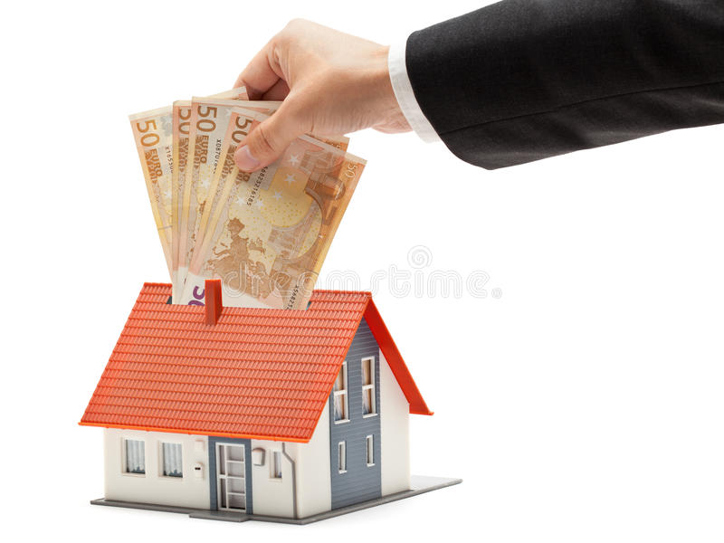 Real estate investment. Man putting Euro banknotes into model house - real estate investment concept stock image