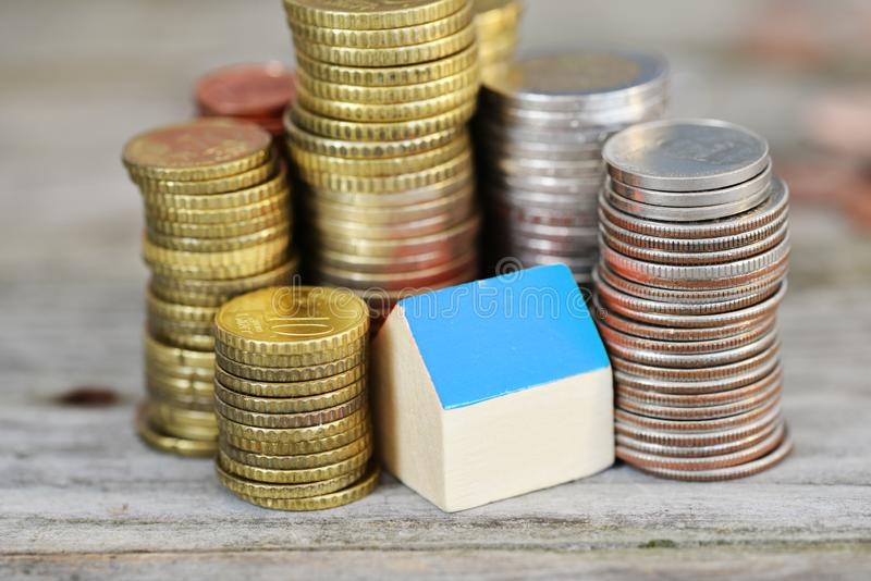 Real estate investment concept with small model house with blue roof surrounded by piles of money royalty free stock photo