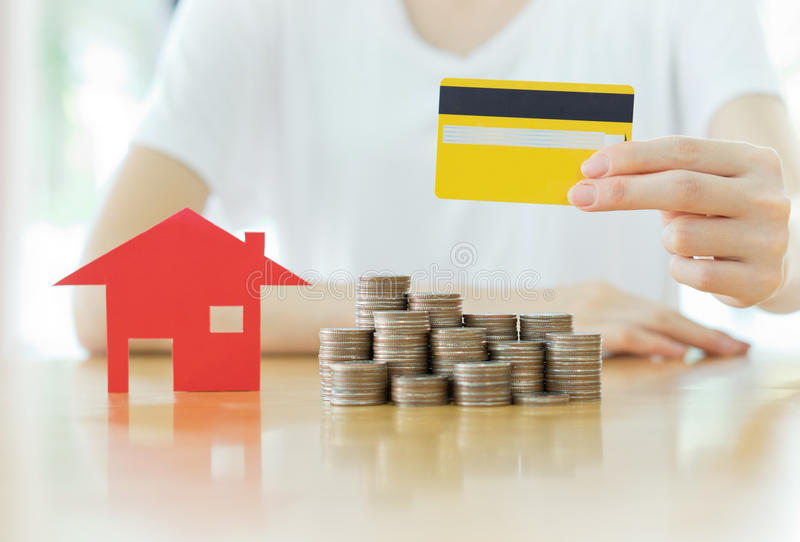 Real estate investment by credit card. House and coins on table royalty free stock photography