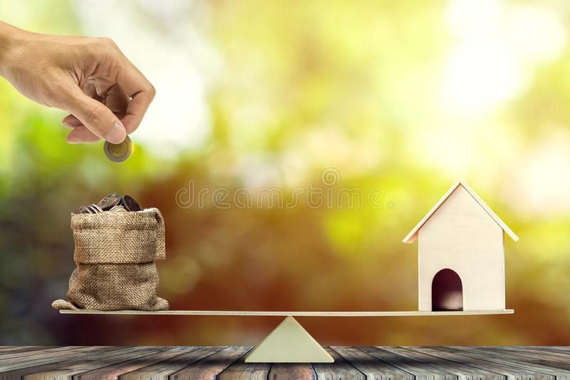 Real estate investment, home loan, reverse mortgage, savings to buy home concepts. House wood model, Hand putting coin into a bags on wood balance scale royalty free stock photo