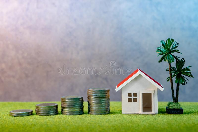 Real estate investment. Property ladder concept. Real estate investment or Home mortgage loan rate. Property ladder concept. Coins stack, house model and table stock photo