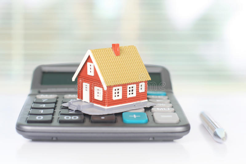 Real estate investment. House and calculator on table royalty free stock photo