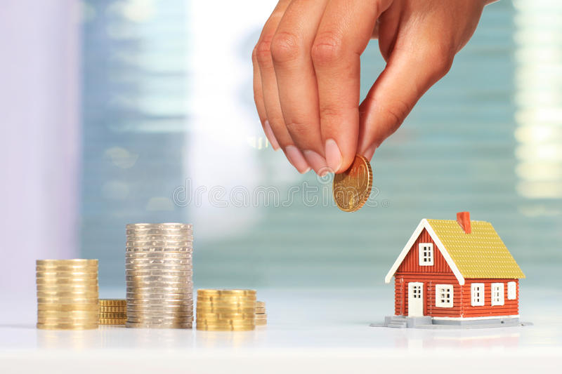 Real estate investment. House and coins on table stock photography